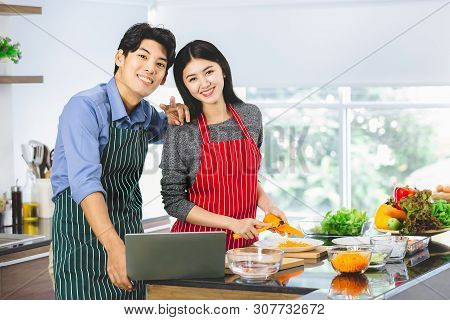 Asian Couple In Apron Standing And Smile To Camera, Man Using Notebook, Woman Chops Carrot, In Kitch