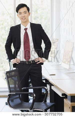 Smiling Handsome Asian Businessman Standing, Touching Chair And Posing, In Office.