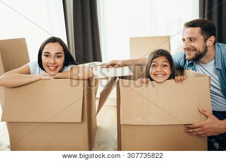 Happy Family Having Fun With Cardboard Boxes While Moving Into New Apartment. Mother, Father And Dau