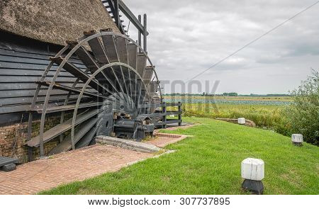 Close-up Of The Paddlewheel Of A Historic Dutch Polder Windmill. The Restored Thatched Wooden Hollow