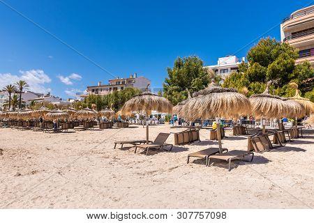 Mallorca, Spain - May 6, 2019: Straw Umbrellas On The Beach In Port De Pollenca (puerto Pollensa), A
