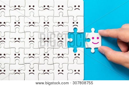 Hand Of A Businessman Chooses A Smiley Face On Piece Of White Jigsaw Puzzle On Blue Background, The
