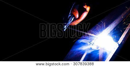 Welder Worker Performs Jump Welding. Man Welder In Protective Gloves Performs Arc-welding Process Of