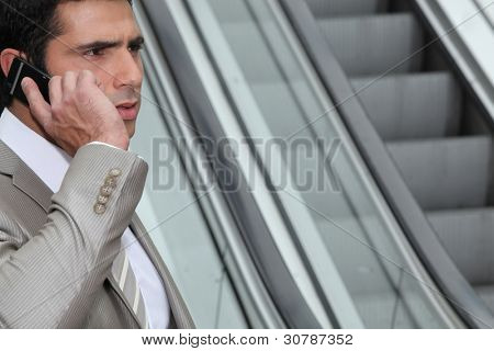 Perturbed businessman using a cellphone by an escalator