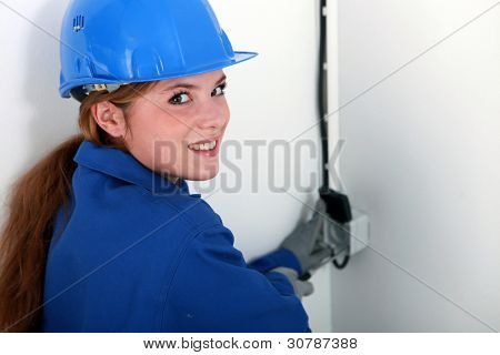 Female electrician fixing wall socket poster