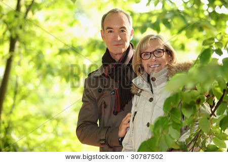 Middle-aged couple walking through park