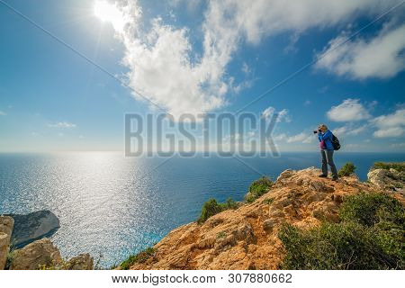 Female Tourist Standing On The Edge Of A Cliff And Photographing The Stunning Cliffs In Shipwreck Co