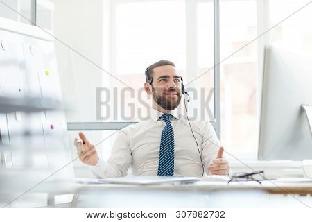 Positive Confident Handsome Hotline Operator With Beard Sitting At Desk With Computer And Answering