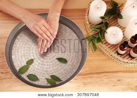 Woman soaking her hands in bowl with water and leaves on wooden table, top view. Spa treatment poster