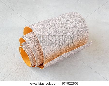 One small roll of extra coarse aluminum oxide sandpaper on a white rough textured background. Abrasive paper for dry sanding. Processing wood and metals, furniture production. Close-up. poster