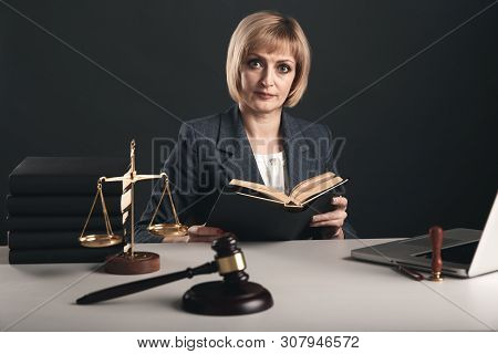 Female Advocate With Juridical Books At Her Workplace. Gavel And Libra On The Desk.