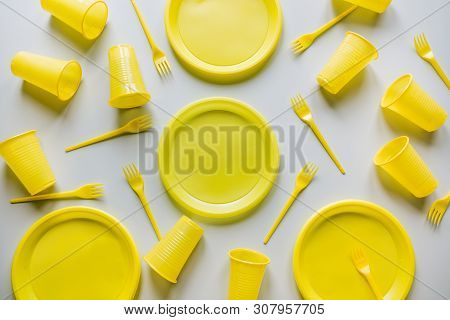 Disposable yellow picnic utensils on grey. Environment eco friendly discarded plastic garbage collection for recycle concept.Top view. Flat lay. Pattern. poster