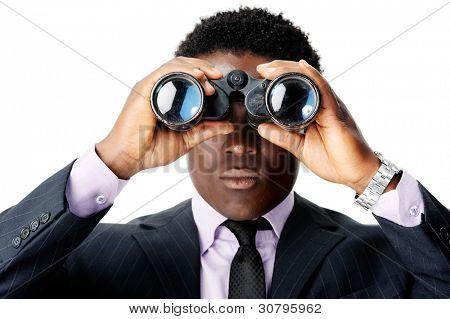 serious binocular businessman looking towards camera. african man