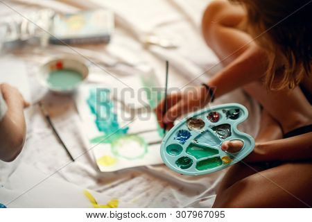 Girl hold palette with temperas