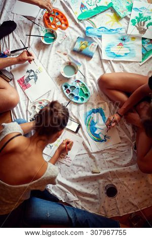 Group of young people painting with temperas