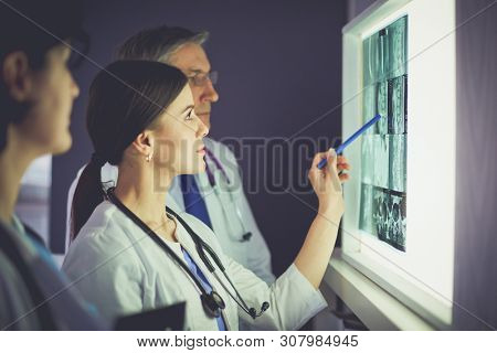 Group of doctors examining x-rays in a clinic, thinking of a diagnosis