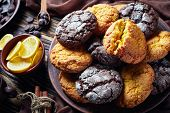 Crinkle cookies. Cracked lemon and chocolate biscuits on an earthenware plate on a rustic wooden table with ingredients, close-up poster
