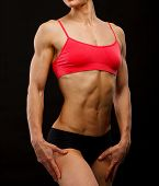 Muscular female body against black background. poster