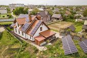 Aerial top view of new modern residential house cottage with blue shiny solar photo voltaic panels system on roof. Renewable ecological green energy production concept. poster