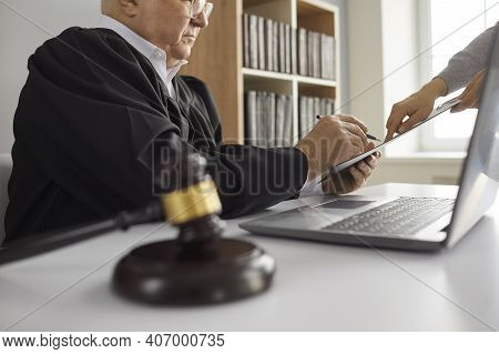 Senior Judge Sitting At Desk At Courthouse And Signing Court Order Given By Lawyer
