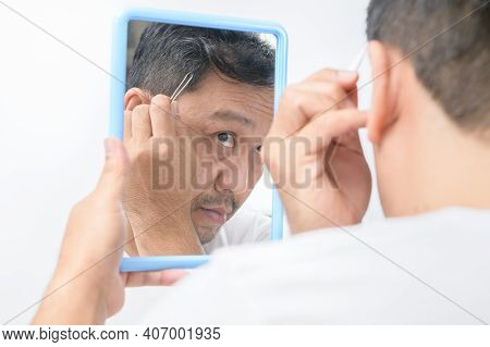 Asian Middle Man Looks In The Mirror And Uses Tweezers To Pluck His Gray Hair Isolated On White Back