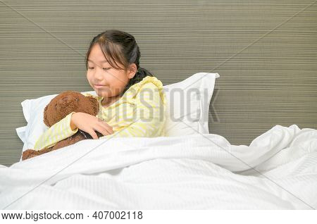 Sweet Little Girl Is Hugging A Teddy Bear, Looking At Bear And Smiling While Lying On Her Bed At Hom