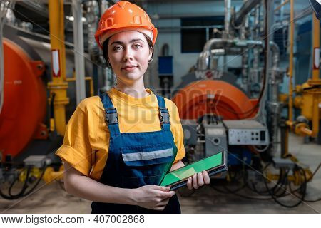 Portrait Of A Caucasian Woman In Uniform And Helmet With A Tablet In Her Hand. In The Background-boi