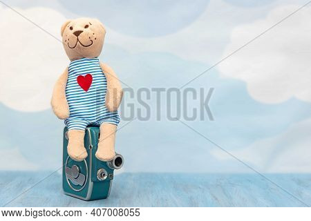 Stuffed Toy Sitting On Old Retro Camera On Sky Pastel Background. Cute Teddy Bear On Empty Backdrop.