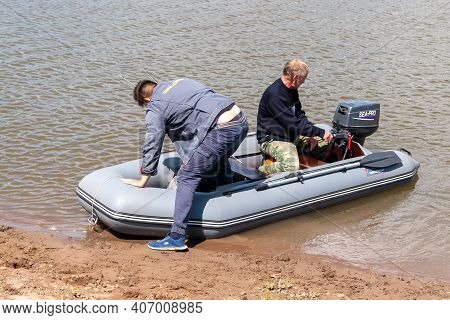 Ufa, Russia, 06.25.2020. Fishermen Are Preparing To Sail In An Inflatable Boat With An Outboard Moto
