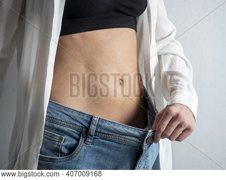 A Slender Woman With A Bare Stomach Shows How She Lost Weight, Holding Her Jeans With Her Hand. The