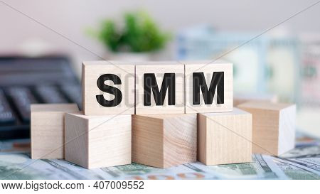 Concept Word Smm On Wooden Blocks On Beautiful Background From Green Flower. The Word Smm On Wood Cu