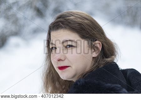 Street Lighting. White Snow. A Girl Of Caucasian Appearance Looks At Us. There Is Snow In The Backgr