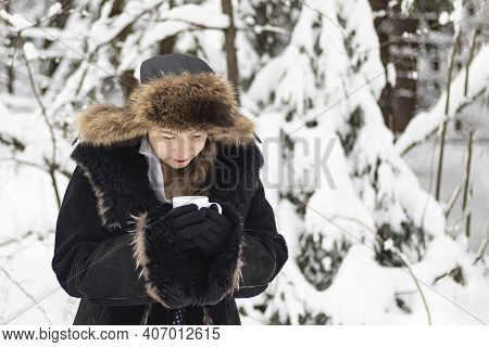 Street Lighting. White Snow. A Girl Drinks From A Cup Of Coffee On A White Background. Close-up.