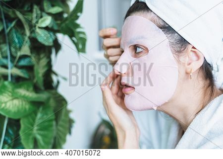 Beautiful Young Woman Uses Sheet Moisturizing Face Mask. Big Mirror With Green Plants. White Bathrob