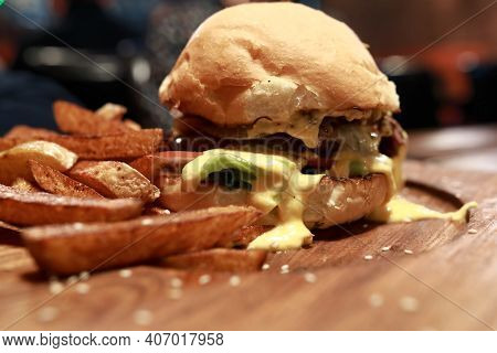 Burger With Fries On Wooden Board In Pub
