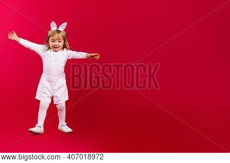 Full-length Photo Of Pretty Baby Girl Wearing Easter Bunny Ears And White Costume, Jumping On Red Ba