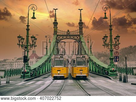 Two Old Yellows Trams On The Liberty Bridge In Budapest. Architecture Of Art Nouveau Style.