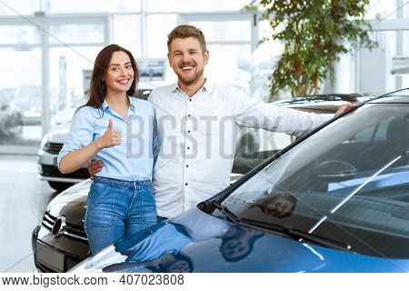 Buying A Dream Car. Portrait Of A Beautiful Young Couple Buying A New Car At The Dealership Handsome
