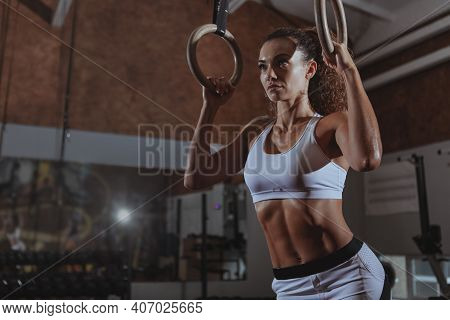 Low Angle Shot Of A Beautiful Curly Haired Sportswoman With Perfect Fit Body Preparing To Exercise O