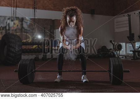 Attractive Curly Haired Female Athlete Chalking Her Hands Before Lifting Heavy Barbell. Fit And Tone