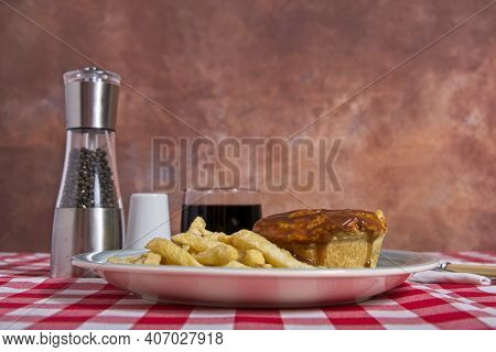 Low View Of Beef Pie With Gravy And Chips On Table With Red And White Table Cloth