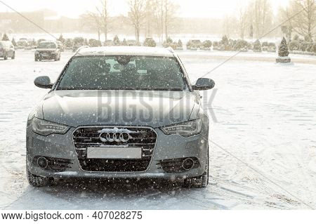 Latvia, Talsi, February 07, 2021: Audi A6 In The Parking Lot During The Winter. Snow Is Falling