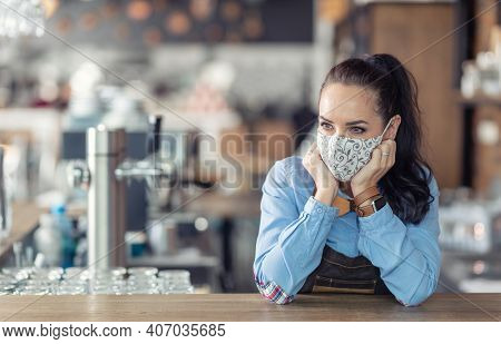 Waitress Stands In A Coffee House With Nothing To Do, Wearing Protective Mask, Waiting For Customers