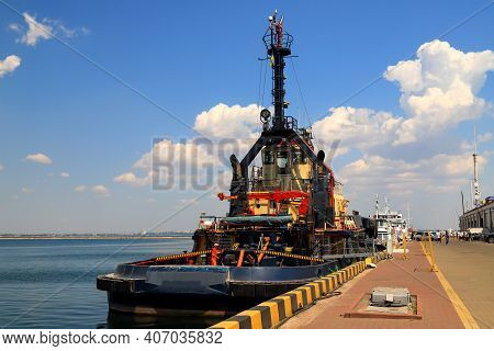 A Large Blue Tug, A Ship In Sea, River Port, Moored Near The Pier. Tugboat Stands In The Seaport, Od