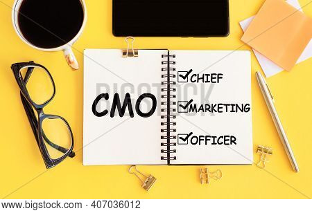 Cmo - Chief Marketing Officer Acronym, With Text On Notepad And Office Accessories On Yellow Desk.