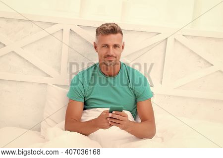 Morning. Online Communication. Mature Man Use Mobile Phone In Bed. Mobile Communication. Cellular Co