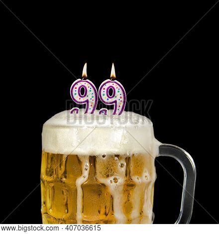 Number 99 Candle In Beer Mug For Birthday Celebration Isolated On Black