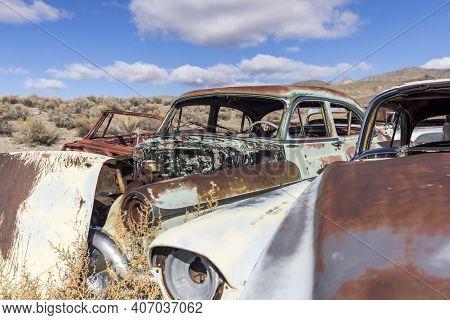Abandoned Vintage Automobiles Clustered Together In A Old Desert Junkyard