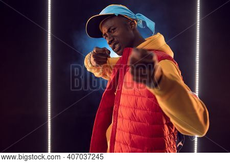 Rapper poses in studio with linear illumination
