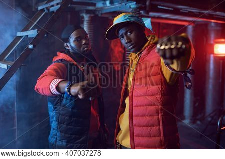 Two rappers with gold jewelry in cool studio